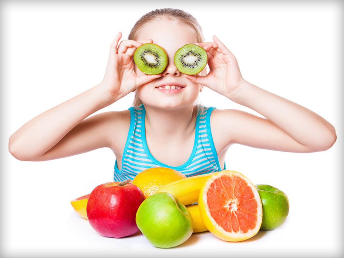Girl with a variety of fruits in front of her, holding two kiwi slices in front of her eyes
